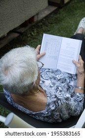 senior woman with short gray hair wearing glasses. the old woman is reading a book in the garden of her house. His back is to the camera. The old woman is wearing a black and white T-shirt