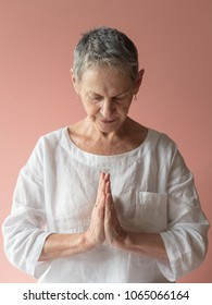 Senior woman with short grey hair and white cloting with hands in prayer position against peach pink background (selective focus)