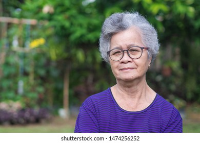 Senior woman with short white hair standing smiling and looking at the camera in the garden. Asian elderly women healthy and have positive thoughts on life make her happy every day. Health concept