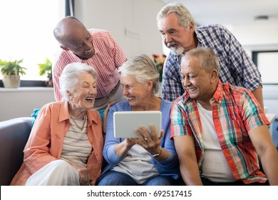 Senior woman showing digital tablet to cheerful friends while sitting on sofa at nursing home