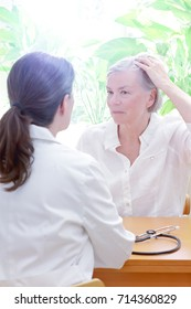 Senior woman showing her thinning hair or alopecia to her female doctor or physician, copy space