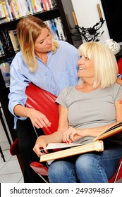Senior woman shows pictures to her home caregiver