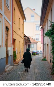 Senior woman silouette in Celje old town in Slovenia. House architecture in Slovenija.