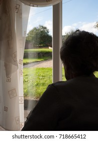 A senior woman sits alone indoors by a window.