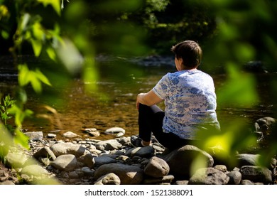Senior woman sitting alone and admiring a river in the forest - Dramatic concept of an old lady standing on the rocks in the mountains and sadly watching the water flowing