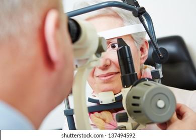 Senior woman sitting behind slit lamp at optician