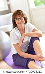 Senior woman sitting by fitness ball