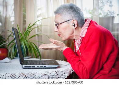 Senior woman sitting by her laptop and talking on a skype call while sending kisses in the camera