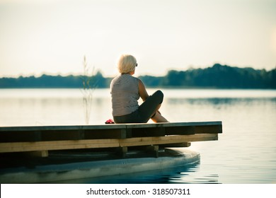 Senior woman sitting by the lake