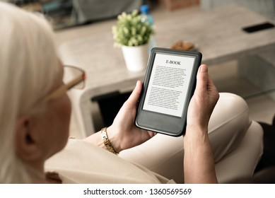 Senior woman sitting by the window, reading an e-book on digital tablet device