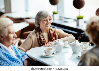 Senior woman sitting in cafe with friends