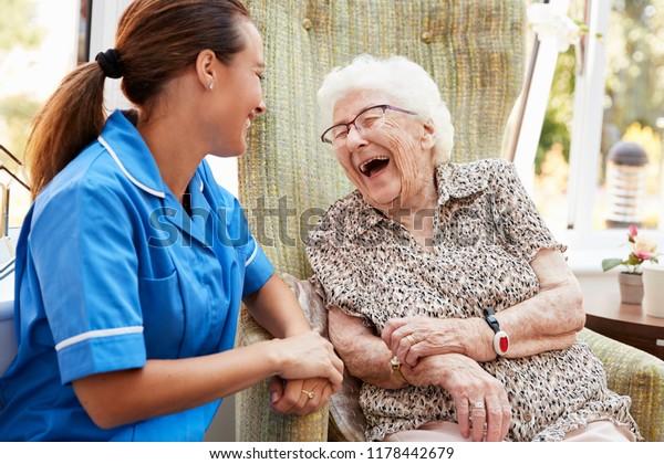 Senior Woman sitzt im Vorsitz und spricht mit Krankenschwestern im Ruhestand
