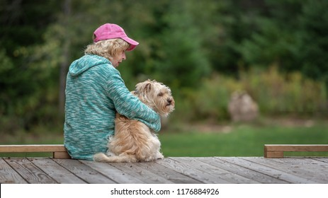 Senior woman sitting with cute little brown dog on the edge of a wooden deck