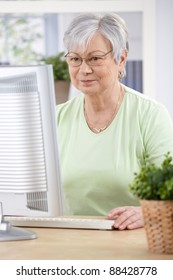 Senior woman sitting at desk, browsing internet at home.?