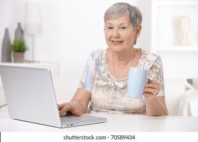 Senior woman sitting at desk using laptop computer, drinking tea.?