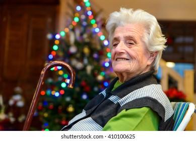 Senior woman sitting near a christmas tree