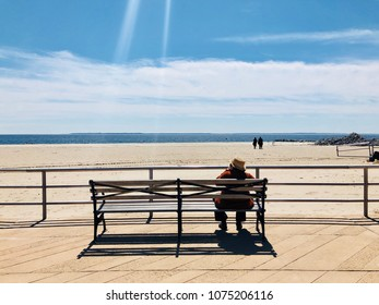 A senior woman sitting on a bench on a beach promenade and watches the ocean in Brighton Beach, Brooklyn, New York. A ray of sun is visible above her.