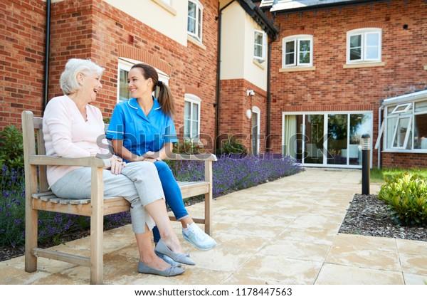 Senderin auf Bänke sitzend und mit Krankenschwester im Ruhestand spricht