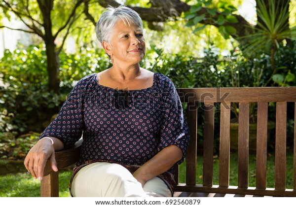 Senior woman sitting on a bench at the park