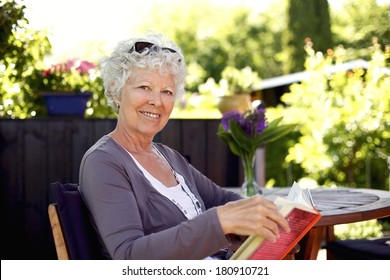 Senior woman sitting on a chair in backyard garden holding a book and looking at camera smiling
