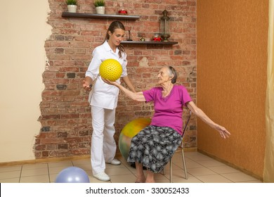 Senior Woman Sitting On A Chair And Holding Spiky Ball During Physiotherapy
