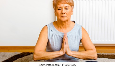 Senior woman sitting on floor with folded hands and making meditation at home.