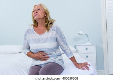 Senior woman sitting on her bed has stomach ache in bedroom