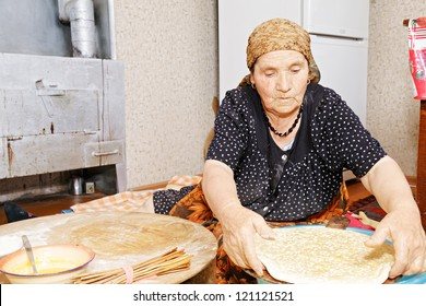 Senior woman sitting on kitchen floor and putting raw bread on wooden board for baking