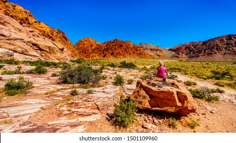 Senior Woman sitting on a large Red Rock while hiking the Guardian Angel Trail in Red Rock Canyon National Conservation Area near Las Vegas, Nevada, United States