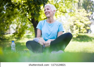Senior woman sitting and resing after workout in park