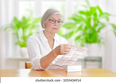 Senior woman sitting at a table in her living room reading the information sheet of her prescribed medicine