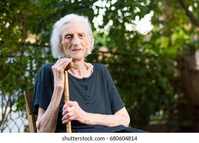 Senior woman sitting with a walking cane outdoors