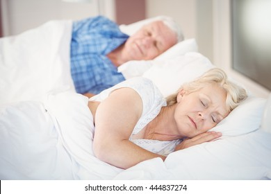 Senior woman sleeping besides husband on bed in room
