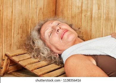 Senior woman sleeps in the wellness sauna and enjoys the healthy heat