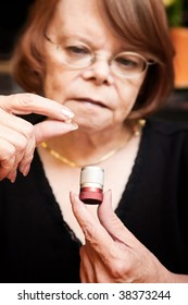 Senior woman with small pill and metal container