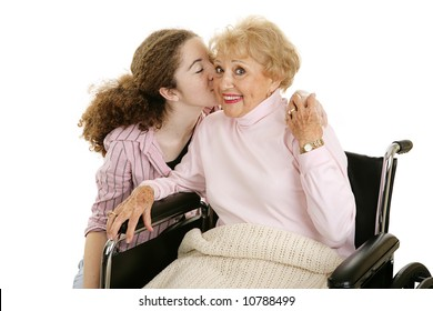 Senior woman smiles as she gets a kiss from her granddaughter.  Isolated on white.