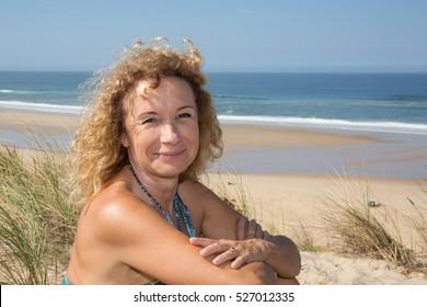 senior woman smiling near ocean beach