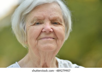 Senior woman smiling in park. MANY OTHER PHOTOS WITH THIS SENIOR MODEL IN MY PORTFOLIO.