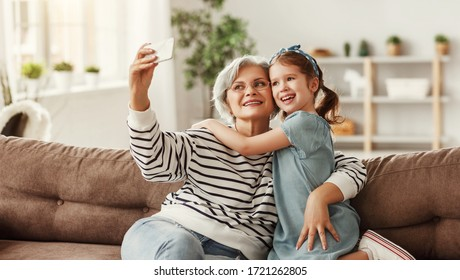 Senior woman smiling and taking selfie with cheerful   girl while sitting on sofa in cozy living room at home