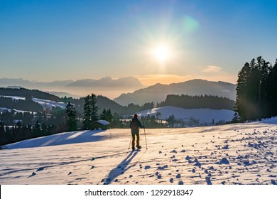 senior woman, snowshoeing in sunset in the Bregenzer Wald area of Vorarlberg, Austria with spectacular view on Mount Saentis, Switzerland