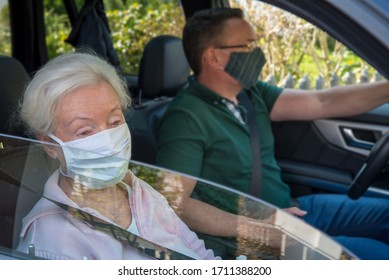 Senior woman and son with face mask driving in the car