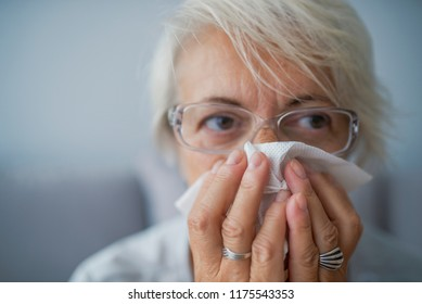 Senior woman in spectacles blowing her nose. Feeling absolutely dreadful. I need some immune system support. A senior woman blowing her nose. Elderly woman having a cold, blowing nose