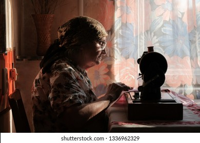 Senior woman in spectacles use sewing machine, silhouette of old dressmaker