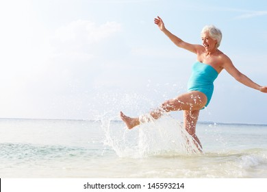 Senior Woman Splashing In Sea On Beach Holiday