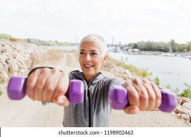 Senior Woman In Sports Clothes Working With Weights Outdoor Workout.