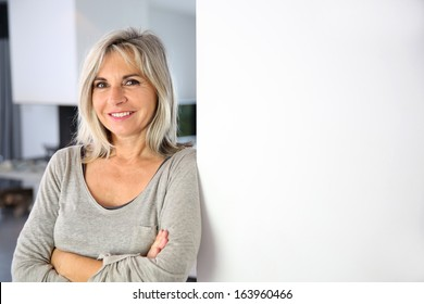 Senior woman standing against white wall