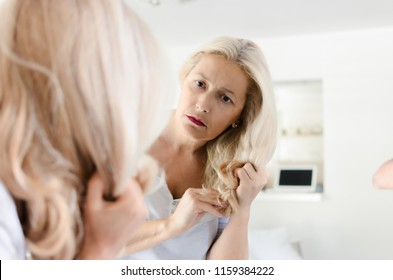 Senior woman standing in front of mirror looking at her demaged hair.