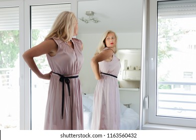 Senior woman standing in front of mirror wearing a long pink dress.