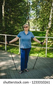 Senior woman standing with Nordic walking poles in summer park. Concept of healthy and active lifestyle of elderly people