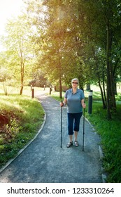 Senior woman standing on footpath with Nordic walking poles in summer park. Concept of healthy and active lifestyle of elderly people